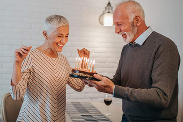 Happy senior couple celebrating special occasion with cake and candles.