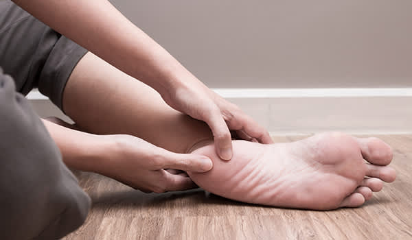 Woman sitting on floor massaging foot.