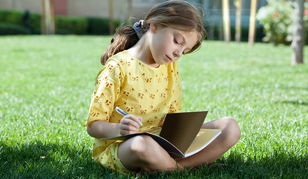 Young girl sitting in the grass writing in her journal.