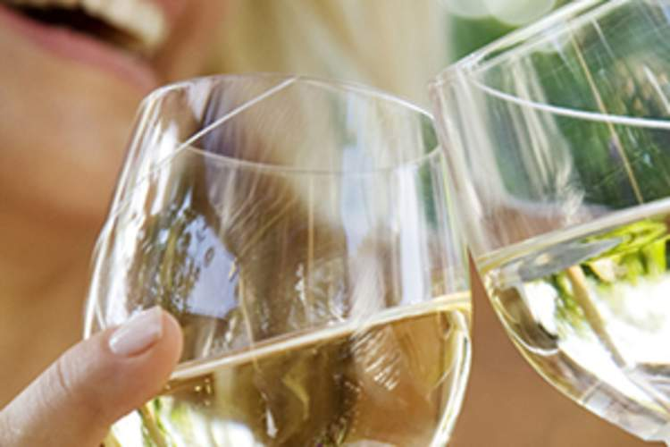 Woman drinking white wine with a friend image.