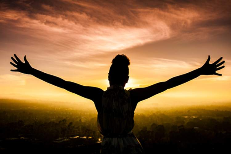 Woman staring at the sunset with her arms wide.
