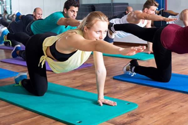 Adults having yoga class in sport club