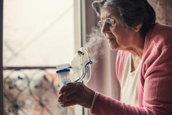 senior woman using nebulizer to help with lung fibrosis