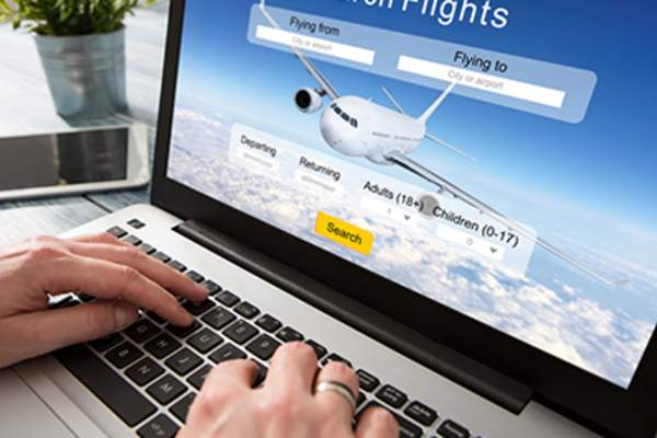 Close up of person booking flights online.
