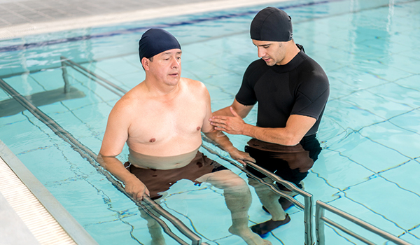 Man undergoing physical therapy in a pool.