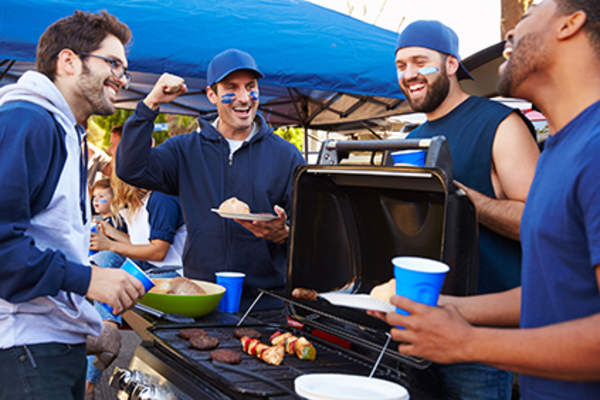 Group of men grilling at a tailgating party.