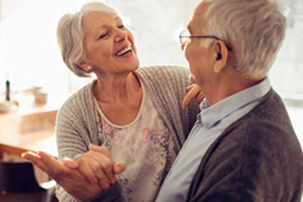 Elderly couple dancing at home image.