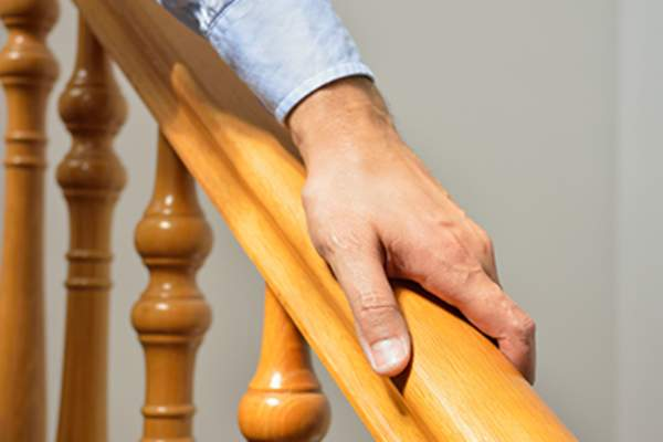 Man holding on to a wooden handrail.