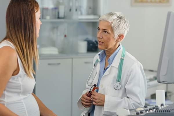 pregnant woman at doctors image