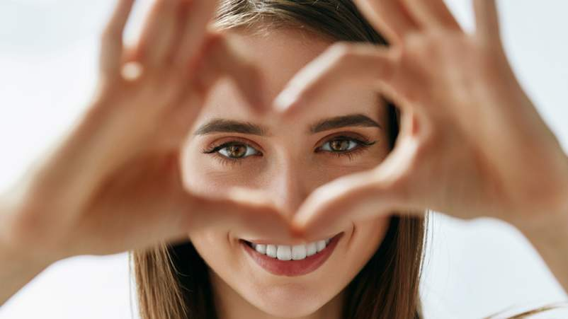 Young smiling woman making a heart with her hands around her eyes.