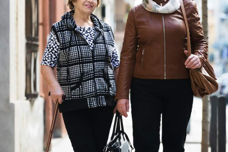 Two older women walking together on the sidewalk.