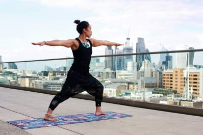 woman doing yoga on rooftop in city