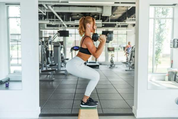 woman squatting and using dumbbells at gym