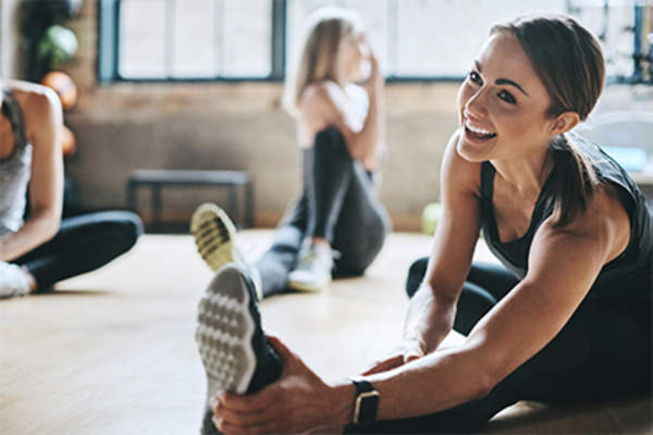 Smiling woman stretching at the gym.