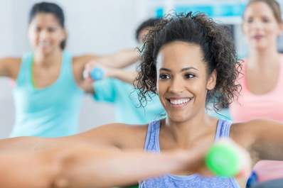 Smiling woman in group exercise class with hand weights.