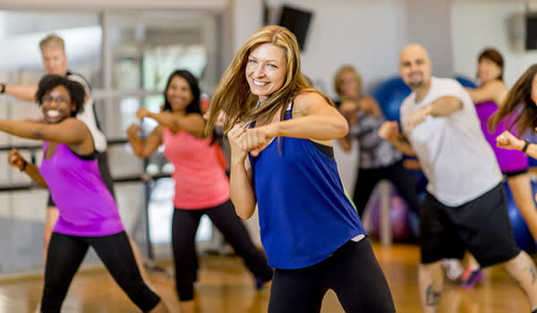 Smiling woman in kickboxing class.