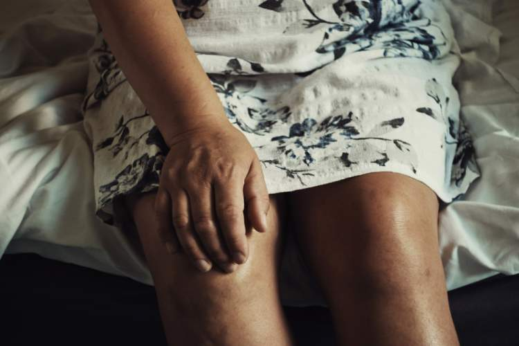 senior woman touching knee