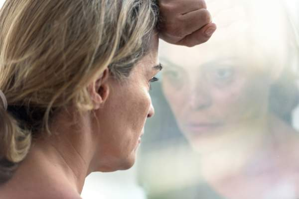 woman looking out window, sad