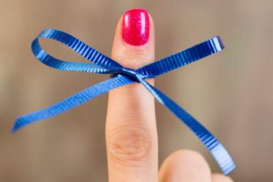 Blue ribbon tied on woman's finger for colon cancer awareness.