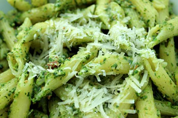 Penne pasta with pesto and cheese.