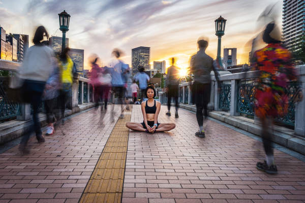 Woman Meditating In a Crowd At Sunset