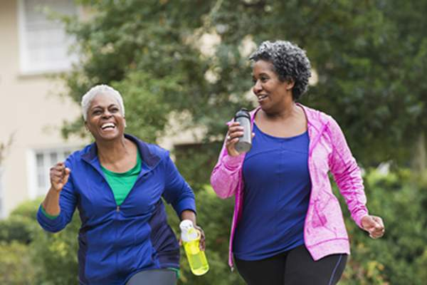 Two senior women exercising together.