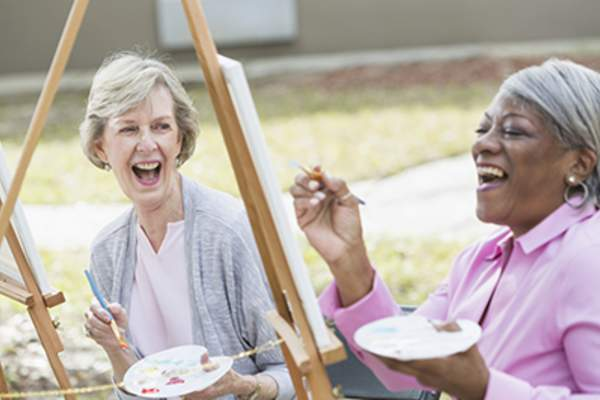 Women laughing and painting outside.