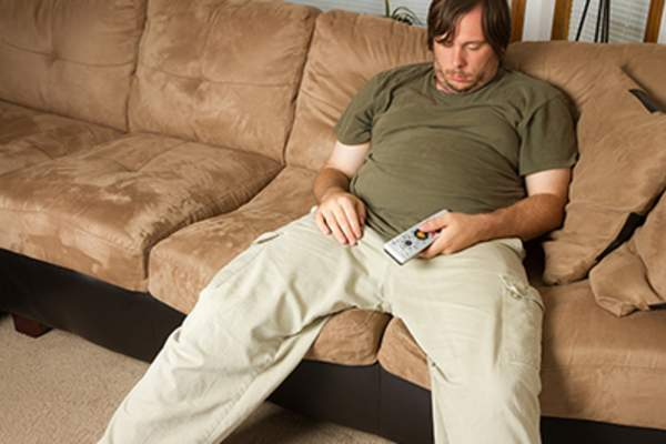 Lazy man asleep with remote in hand on the couch.