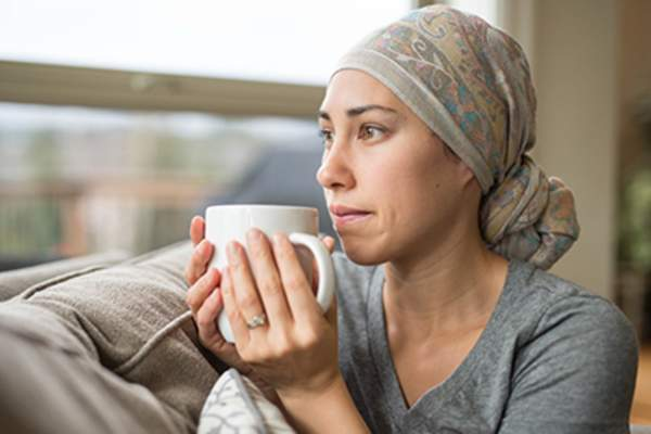 Ethnic young woman with cancer drinking cup of tea on couch