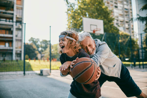 Senior man and grandson playing basketball
