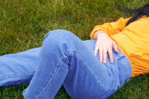 person lying in grass wearing jeans