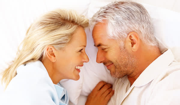 Older couple lying in bed, face to face.