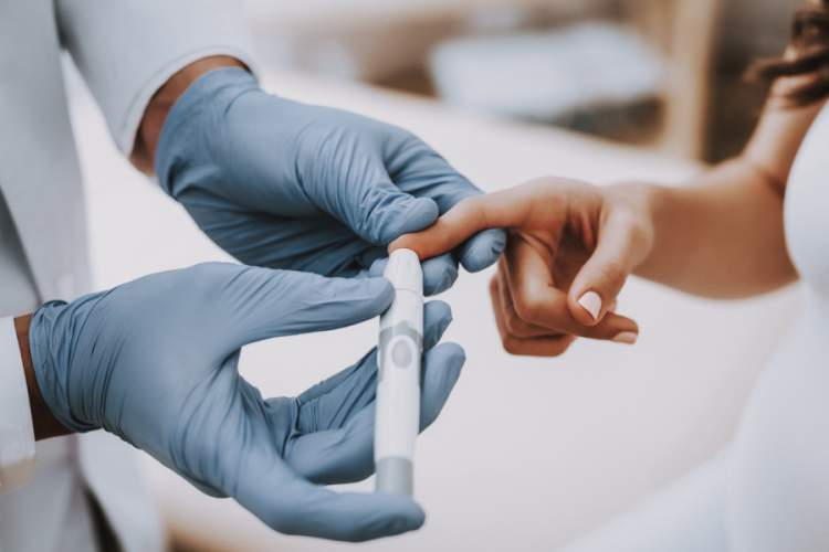 doctor with gloved hands testing patient's blood sugar