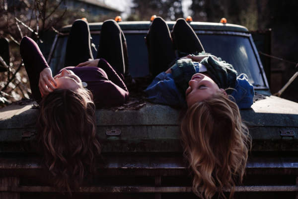 two young women laying down on truck talking