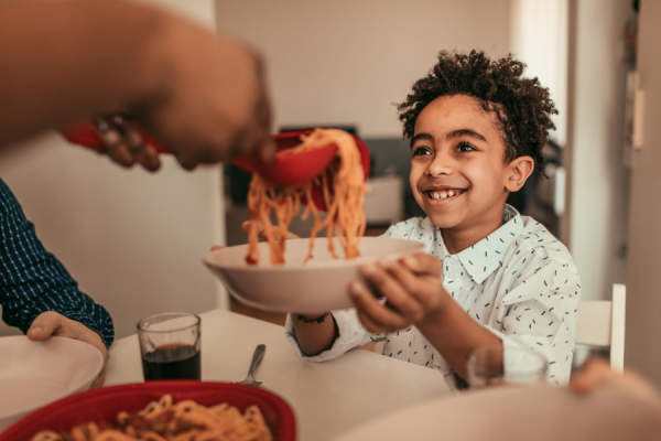 kid being served spaghetti