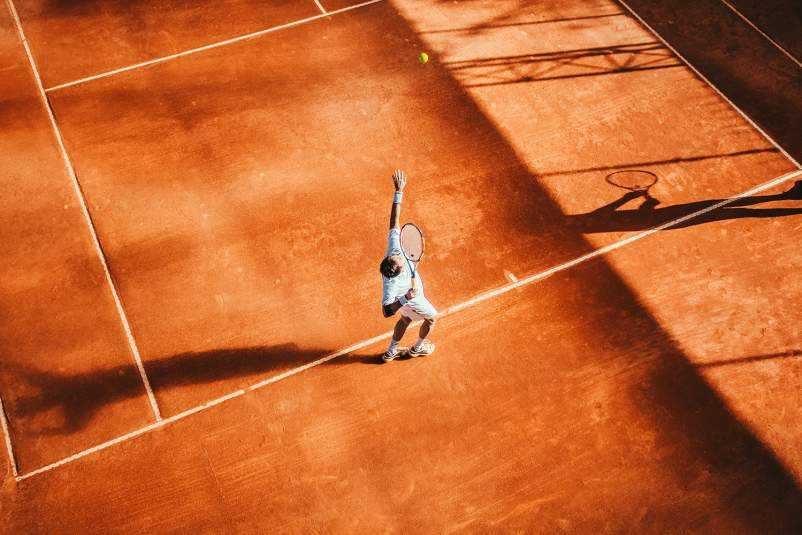 Overhead of man playing tennis on clay court.