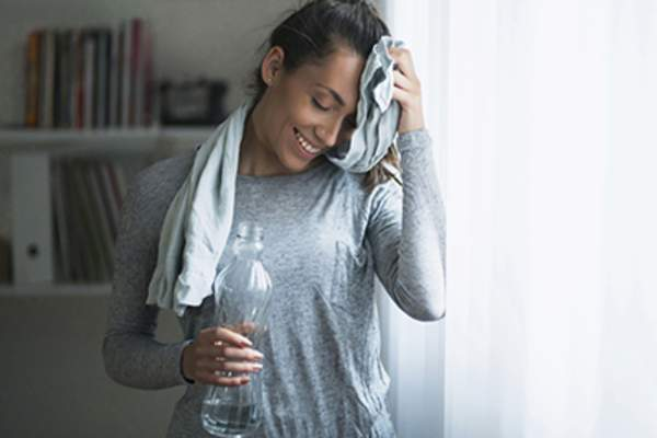 Woman cooling down from a workout with a towel and water.