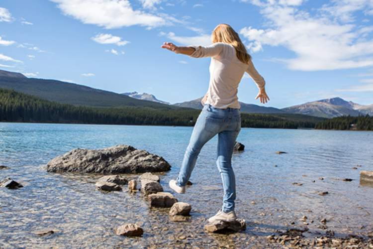 Young woman walking from stone to stone in the water.
