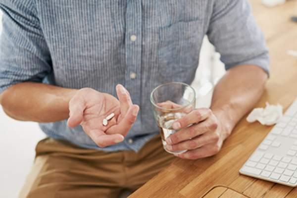 Man taking medicine with glass of water.