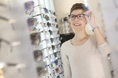 Woman trying on eyeglasses in a store.