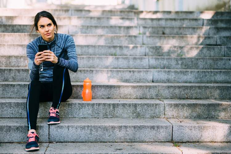 Woman sitting on the stairs listening to music after her run.