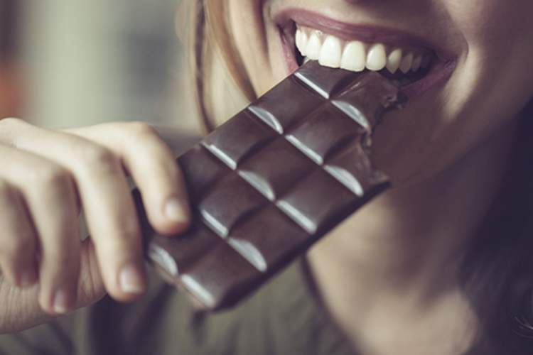 Woman eating dark chocolate bar.