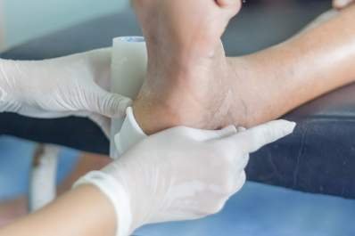 Doctor bandaging a diabetic foot ulcer.