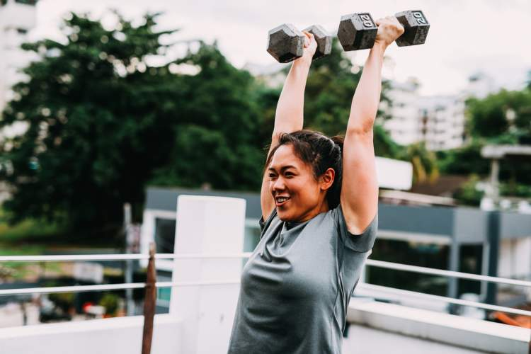 Smiling woman lifting weight.