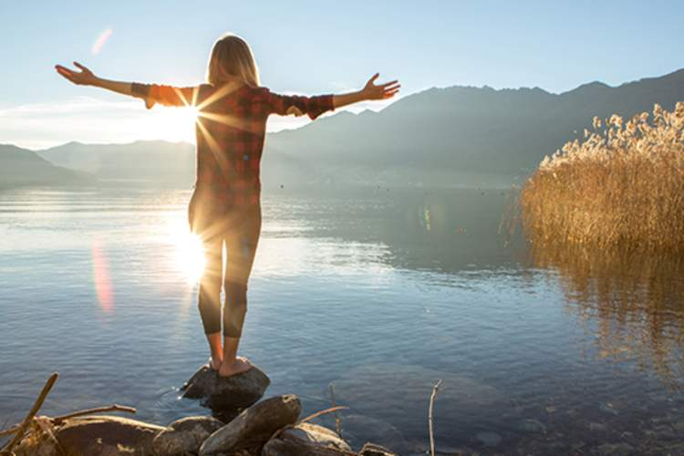 A woman stands on a rock in a lake with her arms outstretched.
