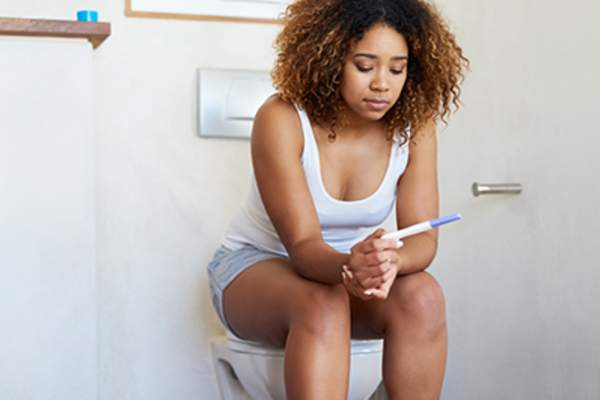 Woman reading pregnancy test while sitting on a toilet.