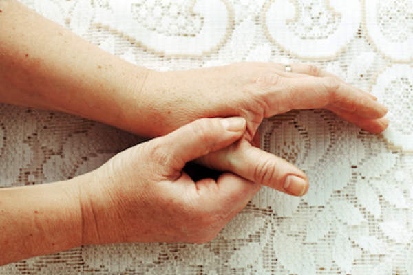 Woman rubbing hand, hand pain concept.