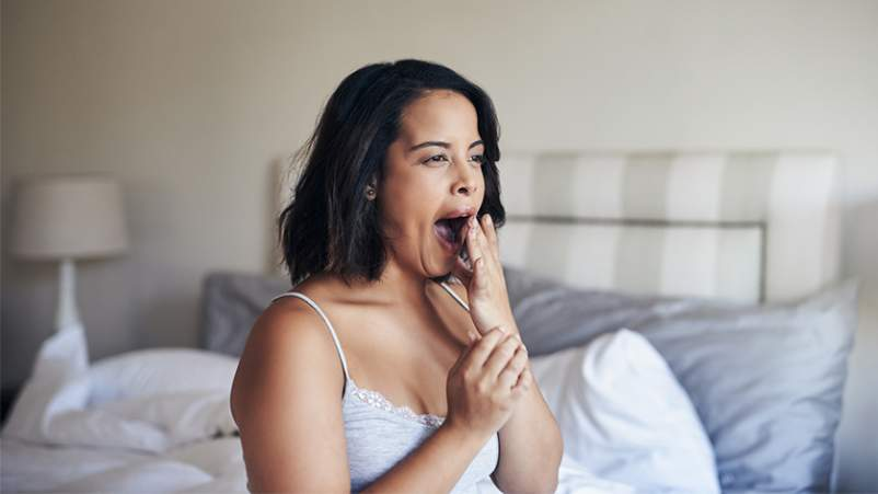 Woman sitting on bed yawning.