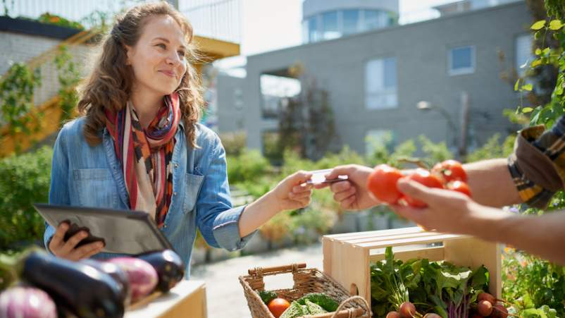 woman shopping for produce at farm stand image