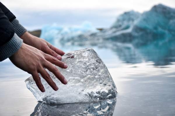 hands touching block of ice